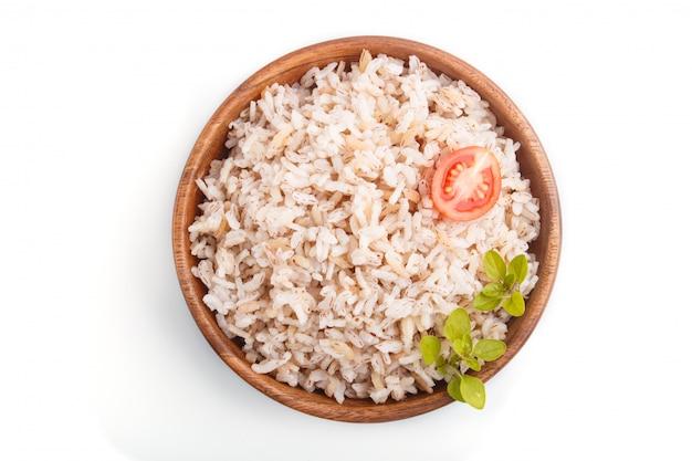 Porridge di riso non lucidato in ciotola di legno isolata su fondo bianco. vista dall'alto.