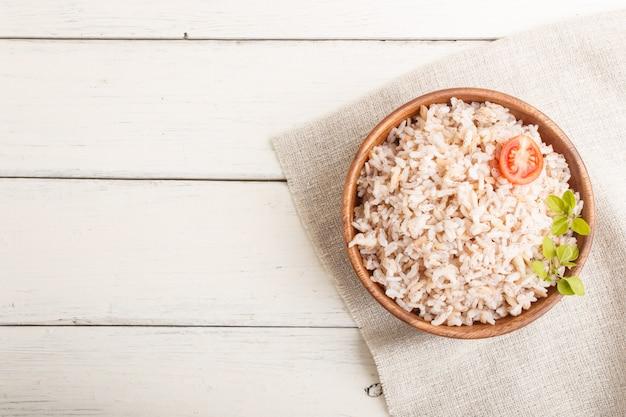 Porridge di riso non lucidato in ciotola di legno su un fondo di legno bianco