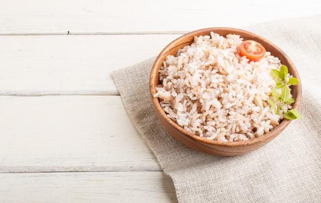 Porridge di riso non lucidato in ciotola di legno su una superficie di legno bianca. vista laterale, copia spazio.