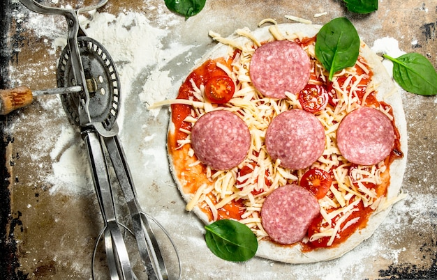 Pizza non preparata con ingredienti sul tavolo rustico.