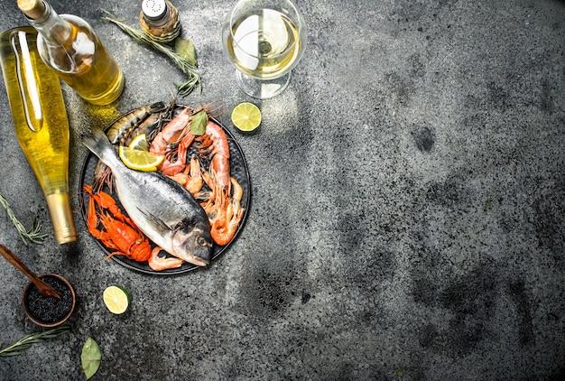 Frutti di mare non trasformati, dorado, gamberetti con vino bianco e spezie sul tavolo rustico.