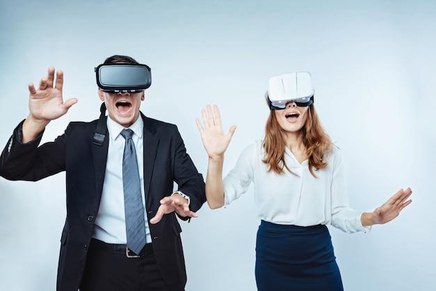 Sensazione irreale. immagine ritagliata di impiegati sbalorditi che gesticolano mentre fanno nuove esperienze e indossano occhiali per realtà virtuale.