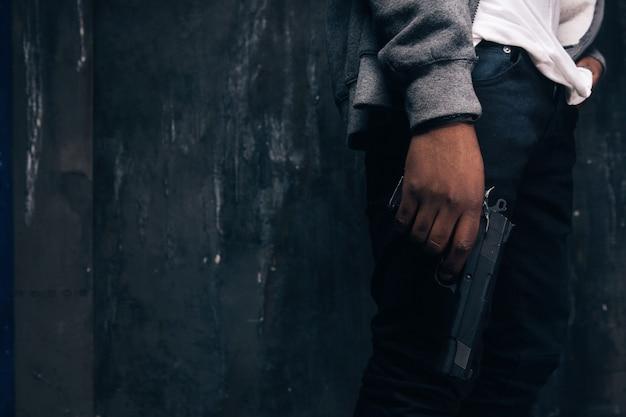Tiro dello studio del primo piano dello stupratore nero armato irriconoscibile