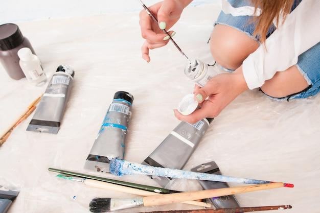 Artista irriconoscibile seduta sul pavimento con i suoi strumenti di lavoro