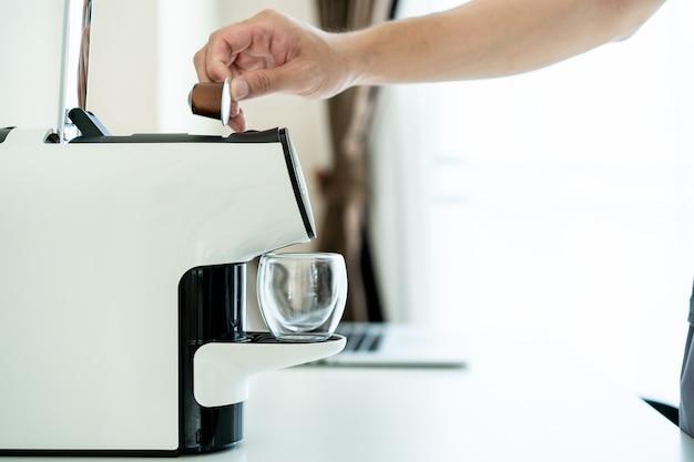 Uomo asiatico irriconoscibile che prepara un caffè espresso utilizzando una macchina da caffè automatica sul tavolo da vicino. una moderna macchina da caffè a capsule.