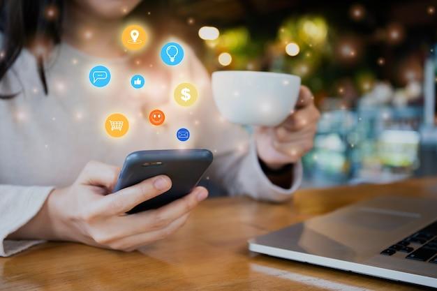 Irriconoscibile giovane donna asiatica che lavora e utilizza lo smartphone mentre si trova nella caffetteria - spazio di co-working. concetto di applicazione per smartphone. connettività e tecnologia delle persone.