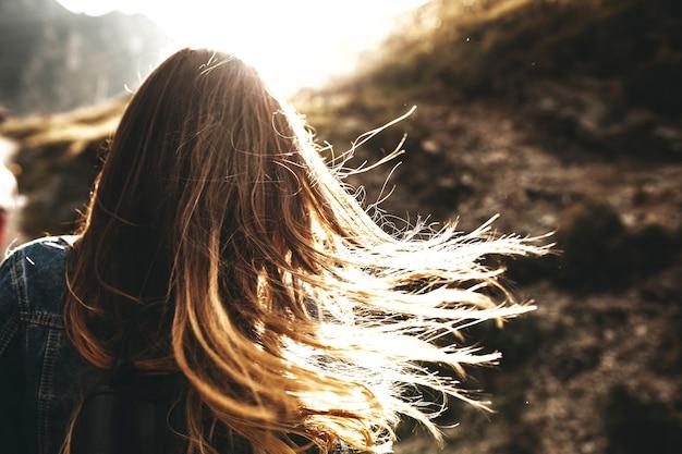 Vista posteriore irriconoscibile di un castano capelli lunghi femminile che gioca al sole razzi al mattino contro il sole.