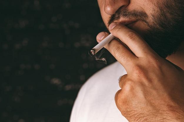 Uomo barbuto irriconoscibile che fuma una sigaretta su sfondo scuro
