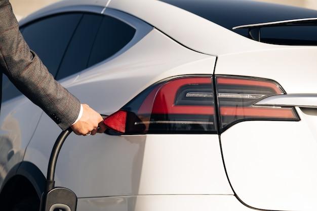 Uomo d'affari irriconoscibile scollegare l'auto elettrica