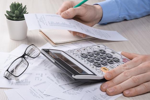 Uomo d'affari irriconoscibile che utilizza la calcolatrice sull'ufficio della scrivania e la scrittura prende nota con calcolare il costo in ufficio a casa. concetto di contabilità finanziaria. tasse, acquisti, gestione dei costi.