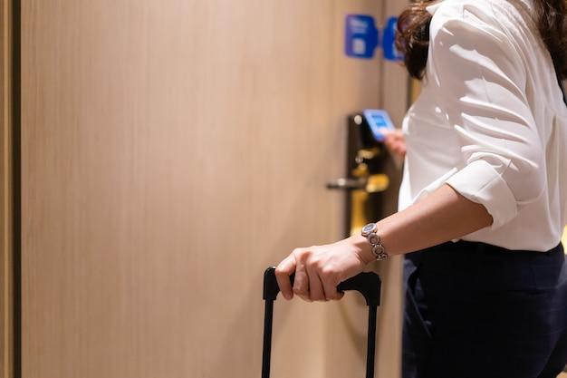 Irriconoscibile donna d'affari in smart casual che trasporta una valigia rigida nella stanza dell'hotel e utilizza la chiave magnetica della camera per sbloccare la porta.