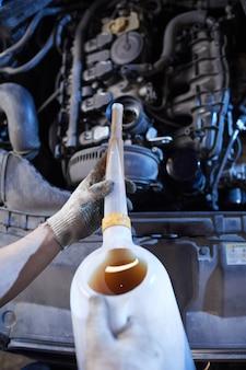 Meccanico di automobile irriconoscibile cambio olio nel motore in officina di riparazione auto, spazio di copia