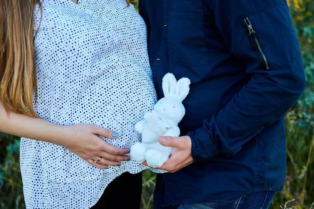 Coppia irriconoscibile che tocca la pancia e che tiene il peluche del coniglietto