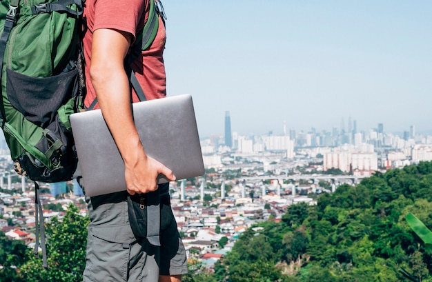 Uomo nomade digitale irriconoscibile che viaggia per il mondo lavorando Foto Premium