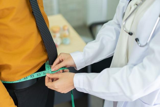 Medico irriconoscibile che misura la vita del paziente maschio obeso utilizzando nastro di misurazione, alimentazione sana - assistenza sanitaria e benessere nei lavoratori. misura nutrizionista sullo stomaco del maschio in ospedale.