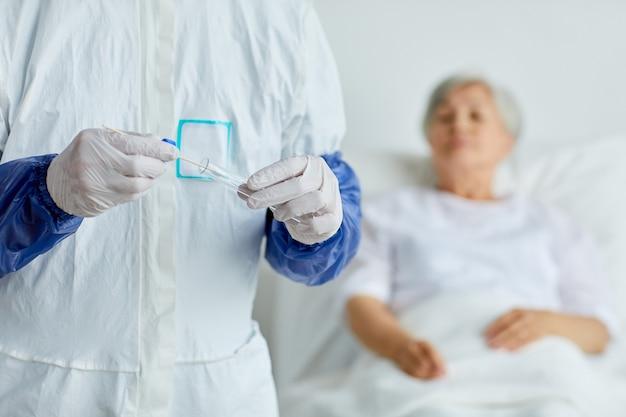 Medico irriconoscibile che mette il bastoncino del campione del tampone nella provetta dopo averlo preso dalla donna senior che si rilassa sul letto dietro