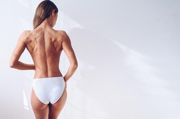 Donna irriconoscibile di misura in biancheria bianca sulla parete bianca isolata. vista posteriore femminile attraente esile muscolare. copia spazio per il testo. cura del corpo, vita sana e sportiva, yoga, concetto di depilazione