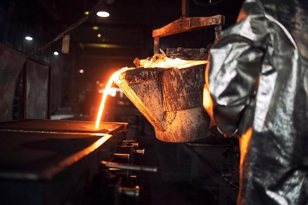Un operaio di fonderia irriconoscibile che riempie stampi di colata con ferro fuso a caldo, produzione di acciaio e metallurgia.