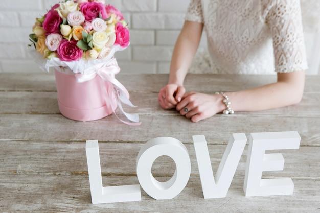 Ragazza irriconoscibile con regalo. mazzo di rose di lusso. boxe fiori colorati in scatola rosa a forma di cilindro. regalo bello e sensuale per l'8 marzo, san valentino, concetto di amore