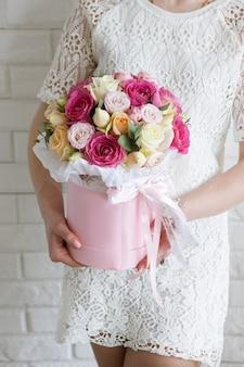Ragazza irriconoscibile con regalo. mazzo di rose di lusso. boxe fiori colorati in scatola rosa a forma di cilindro. bellissimo e sensuale regalo per l'8 marzo, san valentino