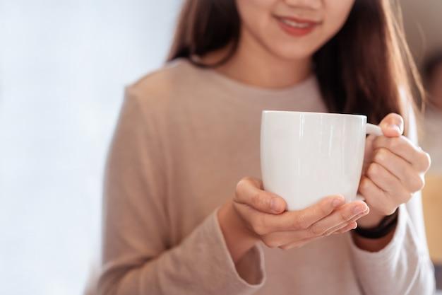 Donna asiatica felice irriconoscibile che tiene una tazza di caffè calda nelle sue mani