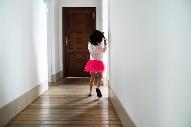 Irriconoscibile bambina che corre sul corridoio di casa con gonna rosa. stile di vita familiare con bambini. i bambini a casa si divertono. tempo libero al chiuso. resta a casa concetto.