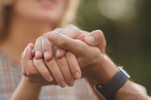 Irriconoscibile coppia di innamorati mano nella mano mentre si gode un appuntamento romantico all'aperto, concentrarsi sul primo piano