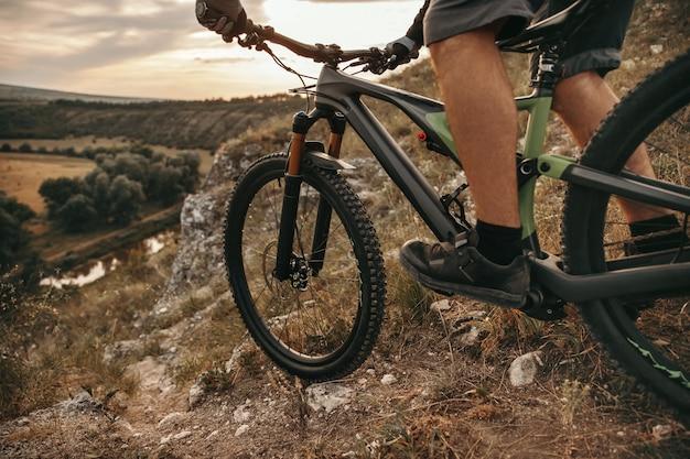 Ciclista maschio irriconoscibile che guida la bicicletta sul sentiero roccioso in terreno montuoso durante il tramonto in campagna