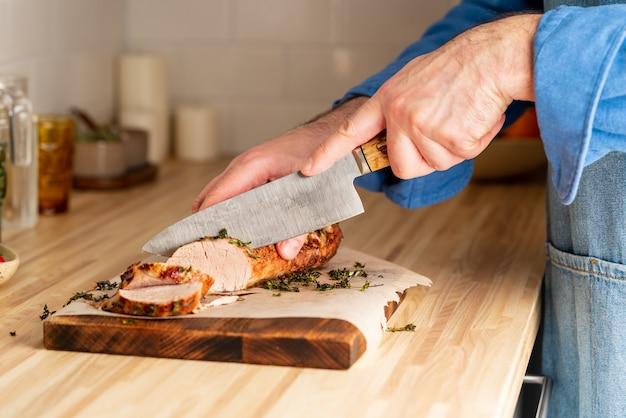 Uomo irriconoscibile taglio con filetto di maiale al forno coltello grande sul tagliere sul tavolo della cucina a casa, affettare fette sottili di carne con lama affilata