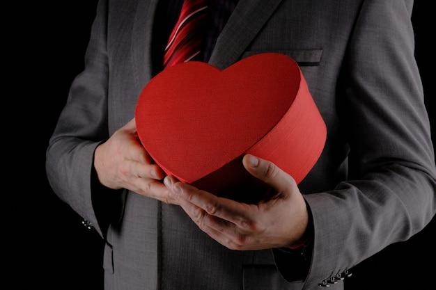 Irriconoscibile uomo in abito grigio porge scatola regalo rosso a forma di cuore, concetto di congratulazioni, sfondo nero