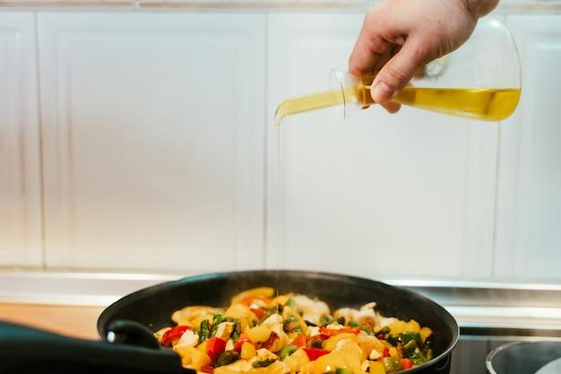 Uomo irriconoscibile che prepara il cibo delle verdure in padella. aggiunta di olio d'oliva. cibo salutare