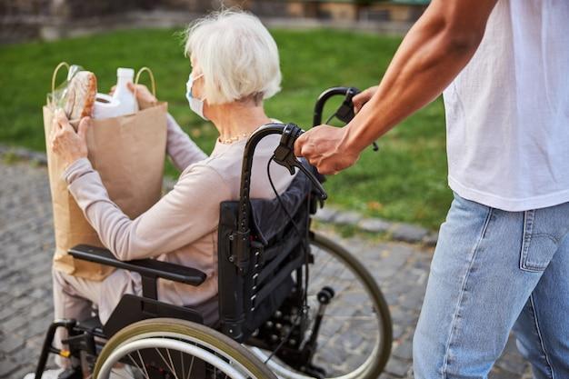 Uomo irriconoscibile che spinge la sedia a rotelle all'aperto mentre una signora anziana tiene in mano una borsa della spesa
