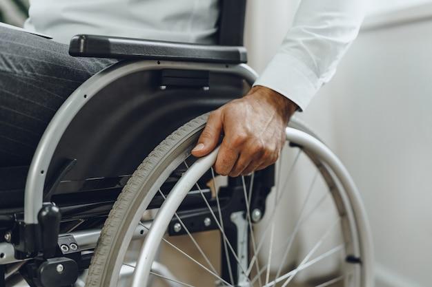 Uomo irriconoscibile seduto in sedia a rotelle da vicino foto