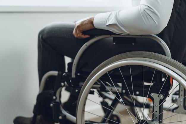 Uomo irriconoscibile seduto in sedia a rotelle vicino foto