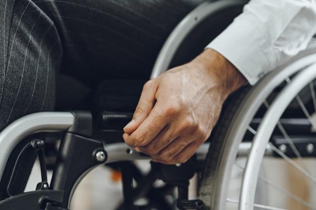 Uomo irriconoscibile seduto in sedia a rotelle si chiuda