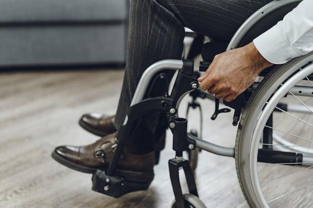 Uomo irriconoscibile che si siede in sedia a rotelle si chiuda