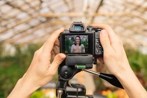 Operatore irriconoscibile che regola la telecamera per girare la rassegna video del blogger asiatico di alimenti naturali in serra