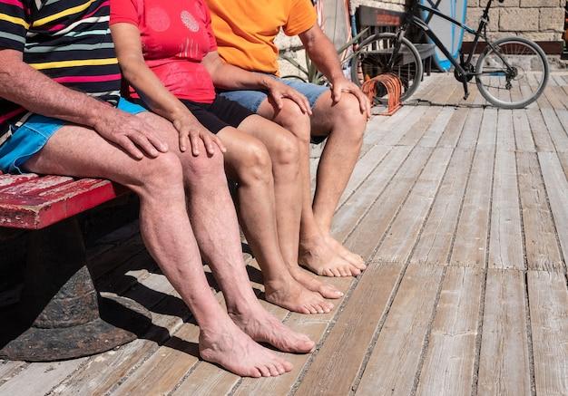 Persone irriconoscibili sedute su una panca di legno vicino al mare. sullo sfondo tavole da surf e mountain bike. tre paia di gambe e piedi nudi. sole estivo splendente