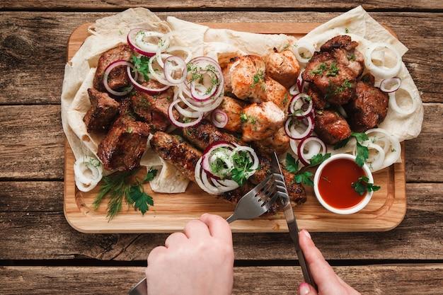 Persona irriconoscibile che mangia carne alla griglia servita con pane pitta, erbe aromatiche, cipolla e salsa di pomodoro, vista dall'alto.