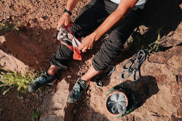Persona irriconoscibile che mette le corde per arrampicarsi. da sopra