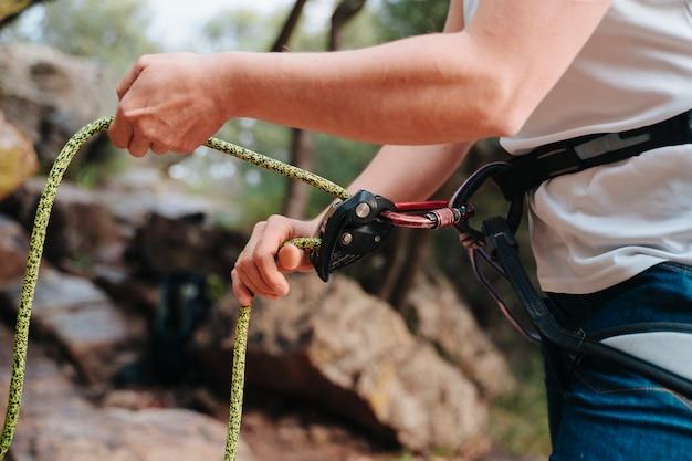 Persona irriconoscibile che mette le corde per l'arrampicata. da sopra