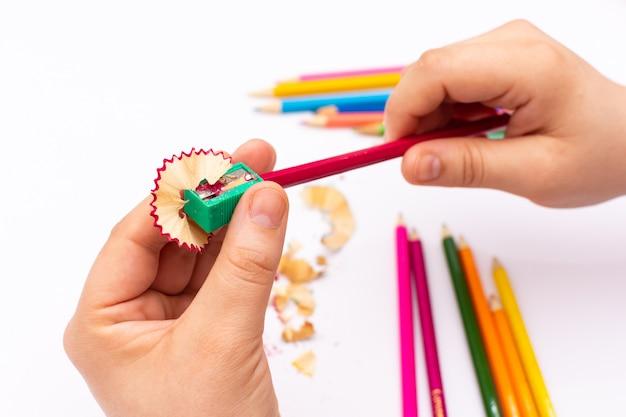 Persona irriconoscibile che affila una matita colorata su una priorità bassa bianca