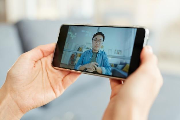 Persona irriconoscibile che prende parte alla videoconferenza online utilizzando smartphone, primo piano orizzontale girato