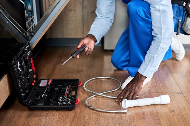 Irriconoscibile tuttofare professionale di aspetto afroamericano in tuta blu riparazione lavastoviglie, utilizzando strumenti di apertura della cassetta degli attrezzi, nel pavimento della cucina a casa. mani ravvicinate