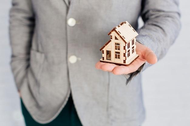 Agente immobiliare irriconoscibile che tiene la figurina della casa