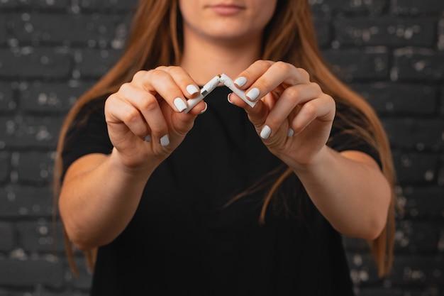 Donna irriconoscibile che rompe la sigaretta nelle sue mani smettere di abitudine si chiuda