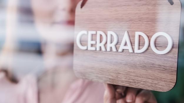 Donna irriconoscibile cambiando aperto a chiuso firmare in spagnolo sulla finestra Foto Premium