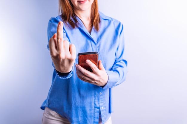 Donna irriconoscibile che tiene in mano uno smartphone che sporge un dito alla telecamera