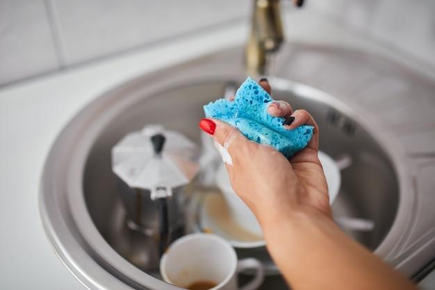 Casalinga donna irriconoscibile che lava i piatti in cucina a casa sul lavandino, stile di vita, attrezzatura domestica.
