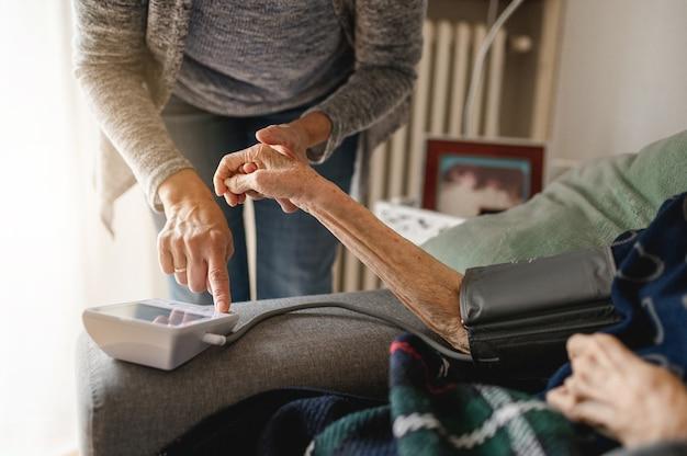 Donna irriconoscibile che misura la tensione con il tensiometro a una persona anziana. assistenza domiciliare e assistenza, concetto di anziani.